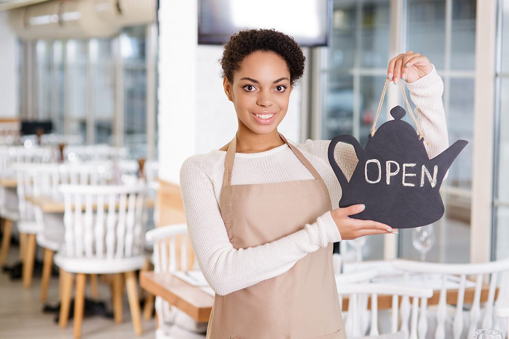 Photo of restaurant employee holding open sign