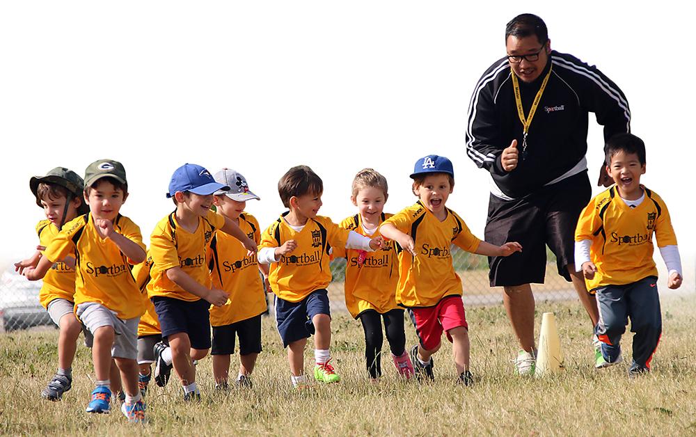Photo of kids wearing Sportball jerseys running through a field