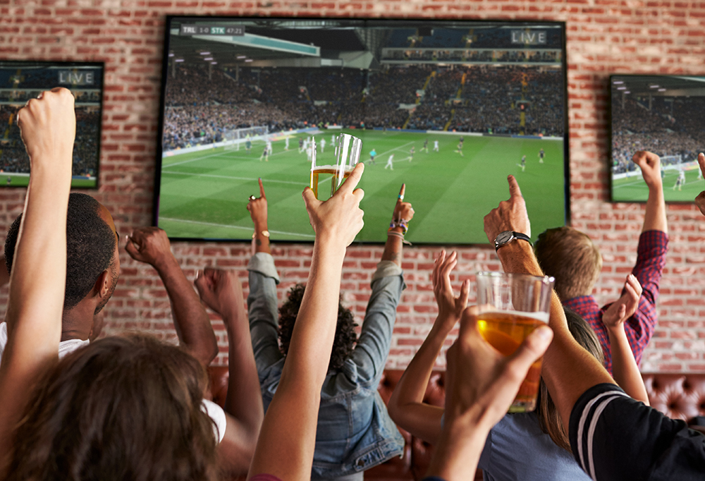 Photo of fans with arms in air watching a sporting event on television
