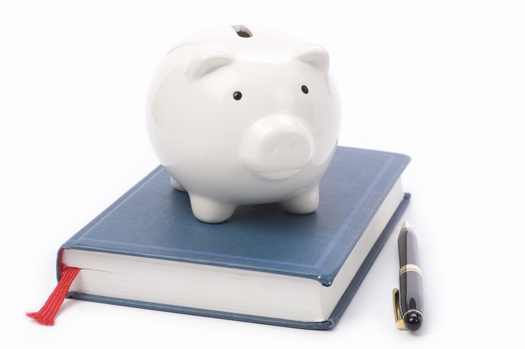 Photo of a piggy bank on top of a book