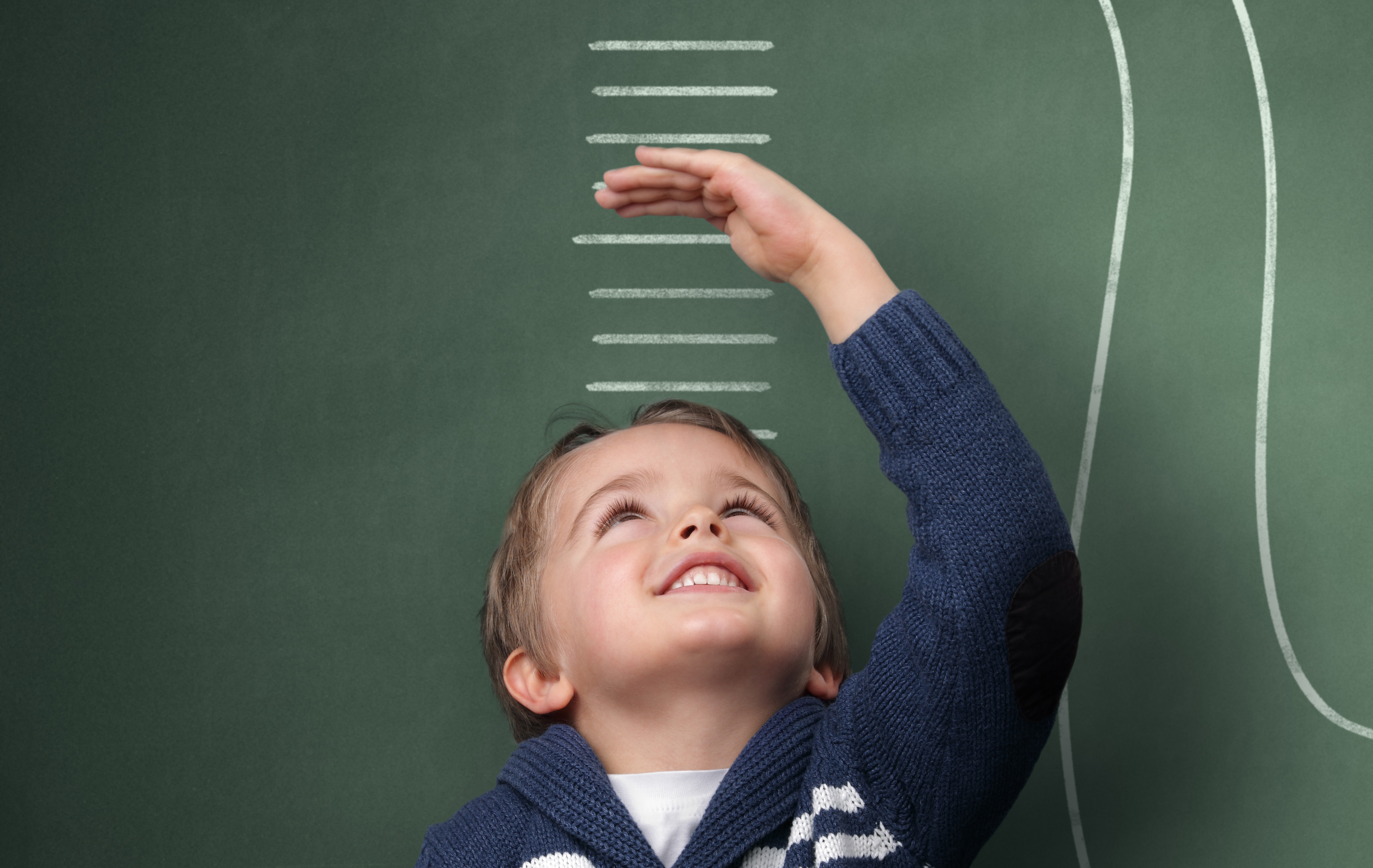 Photo of a young boy measuring his growth in height against a blackboard with chalk dinosaur scale
