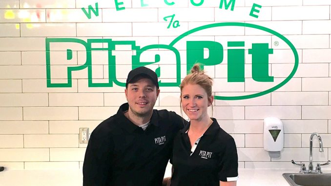 Photo of Pita Pit franchisees Matthew Brown and Stephanie Ervin in front of Pita Pit sign