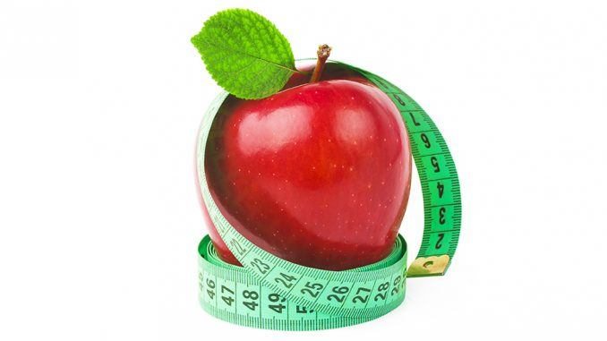Photo of a green tape measure wrapped around a red apple