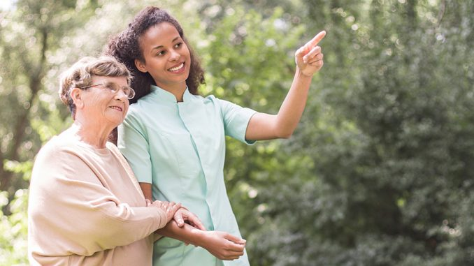 Photo of an elder woman and nurse strolling in the park